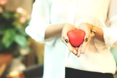 Woman is holding a red heart to giving someone,A gift or a present is an item given to someone . Woman is holding a red heart to giving someone,A gift or a royalty free stock photography