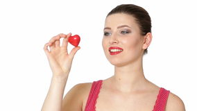 Woman holding red heart . Valentine`s day. Beautiful brunette woman with red lipstick holding red heart in front of face on white background. Valentine`s day stock video footage