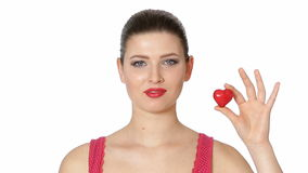 Woman holding red heart . Valentine`s day. Beautiful brunette woman with red lipstick holding red heart in front of face on white background. Valentine`s day stock footage