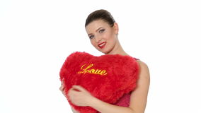 Woman holding red heart . Valentine`s day. Beautiful brunette woman with red lipstick holding red heart on white background. Valentine`s day stock video footage