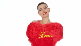 Woman holding red heart . Valentine`s day. Beautiful brunette woman with red lipstick holding red heart on white background. focus on the heart. Valentine`s day stock video