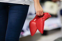 Woman holding red high-heeled shoes Royalty Free Stock Photography