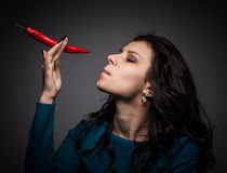 Woman holding red hot chili pepper in mouth Stock Photo