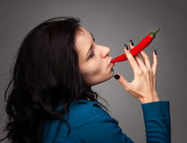 Woman holding red hot chili pepper in mouth Royalty Free Stock Photos
