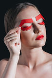 Woman holding red paper brows near face posing for fashion shoot Stock Images