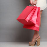 Woman holding red paper shopping bags Stock Photos