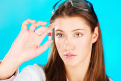 Woman holding red pill. Young woman looking at the red pill, focus on pill Stock Image