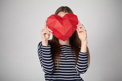 Woman holding red polygonal paper heart shape Stock Images