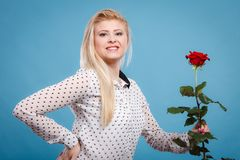 Woman holding red rose flower on blue. Woman holding red rose. Lovely blonde smiling girl with flower studio shot on blue. Romance, holidays, valentine day Stock Photo