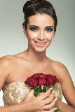Woman holding red rose flowers to her chest and laughs. Beauty young woman holding red rose flowers to her chest and laughs for the camera Stock Photography