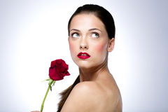 Woman holding red rose and looking up. Portrait of a beautiful woman holding red rose and looking up Stock Photo