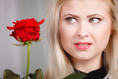 Woman holding red rose near face looking melancholic Stock Photos