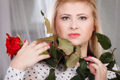 Woman holding red rose near face looking melancholic Stock Photo