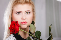 Woman holding red rose near face looking melancholic Royalty Free Stock Image