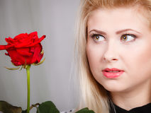 Woman holding red rose near face looking melancholic Royalty Free Stock Photos