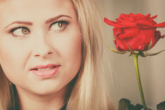 Woman holding red rose near face looking melancholic Stock Photography
