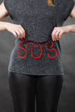 Woman holding red SOS sign, she need help. Sadness, depression, troubles and domestic violence concept. Woman holding SOS sign, she needs help Royalty Free Stock Images