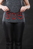 Woman holding red SOS sign, she need help. Sadness, depression, troubles and domestic violence concept. Woman holding SOS sign, she needs help Stock Images