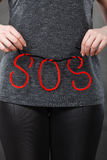 Woman holding red SOS sign, she need help. Sadness, depression, troubles and domestic violence concept. Woman holding SOS sign, she needs help Royalty Free Stock Photo