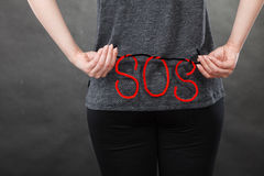 Woman holding red SOS sign, she need help Royalty Free Stock Images