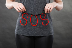 Woman holding red SOS sign, she need help. Sadness, depression, troubles and domestic violence concept. Woman holding SOS sign, she needs help Stock Photo