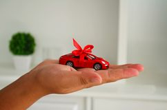 Woman is holding a red sports car in her hand. stock photo
