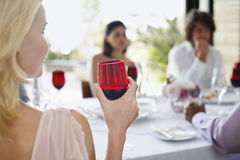 Woman Holding Red Wineglass At Dinner Party Royalty Free Stock Photo