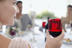 Woman Holding Red Wineglass At Party. Closeup of young woman holding red wineglass with friends in background Stock Image