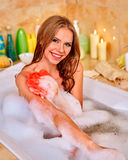 Woman holding red wisp of bast and taking bath Royalty Free Stock Photography