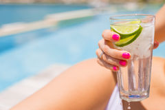 Woman holding refreshing cold drink while sunbathing by the pool Stock Image