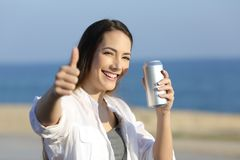 Woman holding a refreshment can looking at you on the beach Royalty Free Stock Image