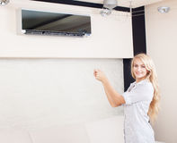 Woman holding a remote control air conditioner Stock Photo