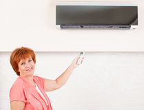 Woman holding a remote control air conditioner Royalty Free Stock Images