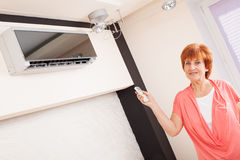 Woman holding a remote control air conditioner Stock Photos