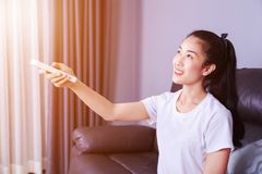 Woman holding a remote control air conditioner on sofa at home. Young woman holding a remote control air conditioner on sofa at home Royalty Free Stock Photos