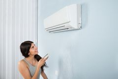 Woman holding remote control air conditioner Stock Image