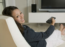 Woman Holding Remote Control While Sitting On Chair Stock Images