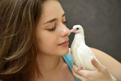 Woman holding a rescue baby pigeon. Young woman helping rescue a baby pigeon stock image
