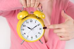 Woman holding retro alarm clock in hand and shows with finger on time royalty free stock photos