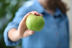 Woman holding ripe green apple on blurred background. Closeup Royalty Free Stock Images