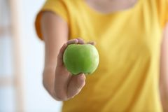 Woman holding ripe green apple. On blurred background, closeup Royalty Free Stock Photography