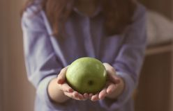 Woman holding ripe green apple  closeup. Woman holding ripe green apple, closeup Royalty Free Stock Images