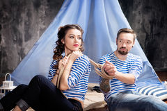 Woman is holding a rope bound man. Sailor in striped vest Royalty Free Stock Photography