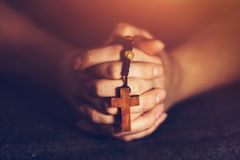 Woman holding a rosary and praying royalty free stock photos