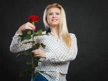 Woman holding rose flower on black. Woman holding rose flower. Attractive blonde young female studio shot dark black background. Beauty, holidays, celebration Royalty Free Stock Image