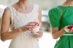 Woman holding rose petals at wedding Stock Photo