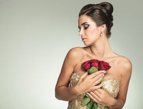 Woman holding roses to her chest and looks to side Royalty Free Stock Images