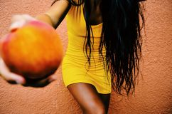 Woman Holding Round Fruit While Leaning on Orange Wall Stock Photography