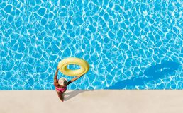 Woman holding rubber ring overhead at poolside. Aerial view of woman in straw hat standing at poolside, holding yellow inflatable ring overhead and looking at Stock Photography