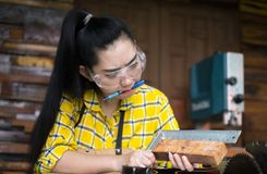 Woman holding ruler and pencil while making marks on the wood the table in the workshop royalty free stock photos